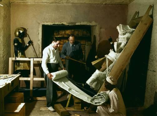Howard Carter, Arthur Callender ve bir Mısırlı işçi, 29 Kasım 1923'te mezar odasında heykellerden birini sararlarken